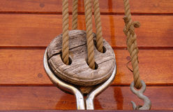 Rope with a knotted end tied around a cleat on a wooden pier - Nautical rope Royalty Free Stock Images