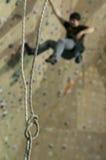 Rope la boucle et l'homme sur s'élever sur le mur d'intérieur de pratique image libre de droits