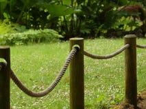 Rope la cerca con los posts de madera de la cerca en jardines en Inglaterra imagenes de archivo