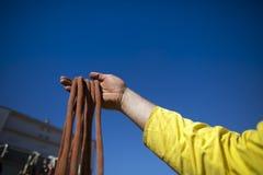Rope la mano masculina del inspector del técnico del acceso que examina 10 cuerda secundaria de la parte posterior de la segurida imagen de archivo