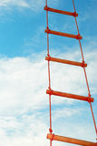 Rope ladder against a blue sky. Wooden rope ladder on a blue sky background Stock Image