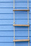 Rope ladder. On the blue wall for background Stock Photos