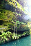 Rope ladder on the steep rock with lens flare Stock Photos