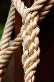 Large white rope that bound. Rope large white multi-strand bound to a wooden pole massively stock photo