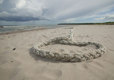 Rope laying in sand. GN. Rope laying on a sand beach whit storm clouds on the sky. GN royalty free stock image