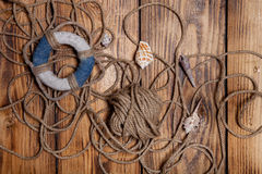 Rope and lifebuoy on old wooden burned table or board for backgr Royalty Free Stock Photos