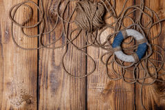 Rope and lifebuoy on old wooden burned table or board for backgr Royalty Free Stock Images