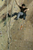 Rope loop and man on climbing on indoor practice wall Royalty Free Stock Image