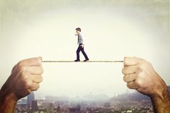 On a rope. Man hovering on a rope held by two hands Stock Images