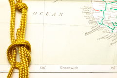 Rope and map. Gold color rope cable with simple knot put on old and vintage paper map represent the detail of city name and destination royalty free stock photography