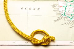 Rope and map. Gold color rope cable with simple knot put on old and vintage paper map represent the detail of city name and destination stock images