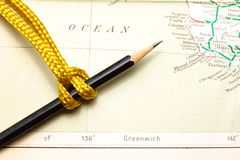 Rope and map. Gold color rope cable with simple knot put on old and vintage paper map represent the detail of city name and destination royalty free stock photo
