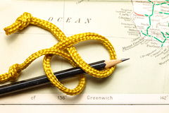 Rope and map. Gold color rope cable with simple knot put on old and vintage paper map represent the detail of city name and destination stock photo