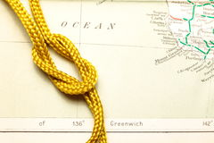 Rope and map. Gold color rope cable with simple knot put on old and vintage paper map represent the detail of city name and destination royalty free stock images