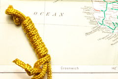 Rope and map. Gold color rope cable with simple knot put on old and vintage paper map represent the detail of city name and destination stock image