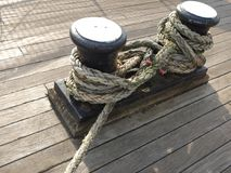 Rope and mooring cleats. Heavy rope and mooring cleats on timber decking, Glasgow, 2017 Royalty Free Stock Photos