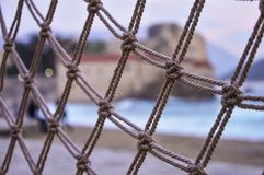 Rope net pattern with a beach and old town in the background royalty free stock image