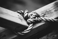 Rope with node. On wooden beam. Black and white film style colors Stock Image
