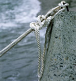 Rope of an old boat tied to . Rope of an old boat tied to a stone shore Royalty Free Stock Images