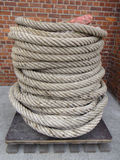 Rope on pallet. Coil of heavy duty rope on a wooden pallet with red brick wall behind Royalty Free Stock Photo