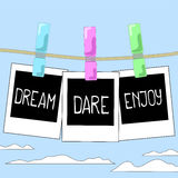 Rope with photo frames on cloudy sky background. Motivation words Dream, Dare, Enjoy on instant photos. Stock Photography