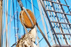Rope pulley and ropes on an old sailing ship. Close-up of a rope pulley and ropes on an old sailing ship against a blue sky royalty free stock photography