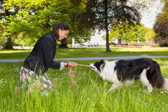 Rope pulling with her dog Stock Photography