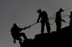 Rope Rescue. Rescuers assisting a team member rappelling down a rock