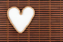 Rope in the shape of a heart with a place for your text, lying on a bamboo mat. Royalty Free Stock Photos