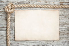 Rope, sheet of paper and wood background Stock Image