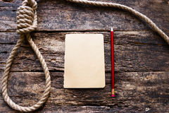 Rope with a slipknot. And a suicide note royalty free stock photo