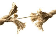 Rope splitting apart held together by one thread. Close-up of a rope splitting apart held together by one last thread, concept of fragility and division, with stock images