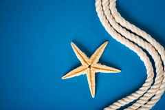 Rope and starfish. On blue Royalty Free Stock Photography