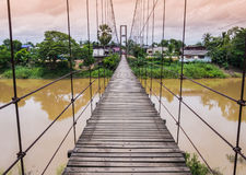Rope suspension bridge across a river in flood, Thailand. Rope suspension bridge across a river in flood at dusk, Thailand Royalty Free Stock Image