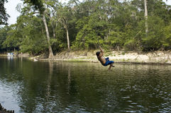 Rope Swing 1. A boy is about to drop into the river on the rope swing Royalty Free Stock Image