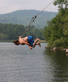 Rope Swing. Man jumping into lake off a rope swing Royalty Free Stock Photo