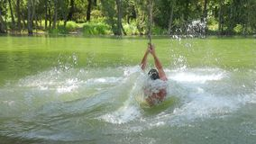 Rope swing river jump. Guy jumping from rope swing hitting the water too soon, slow motion from 60 FPS stock video footage