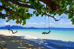 Rope swings on a beach of Kradan island. Rope swings on a beach of Koh Kradan with Koh Muk in the background, in the Andaman Sea, Thailand stock images