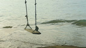 A rope swings on the beach, slow motion stock footage