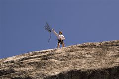 Rope Throw. A climber tosses a rope from the top of a cliff Stock Photo