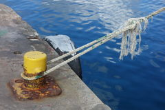 A rope thrown over a stanchion at a concrete dock Stock Photo