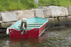 Rope Tie. This red skiff is tied by a rope onto this rock barrier Stock Image