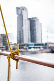 Rope tied around hook on handrail. Outdoor shot city by the water in background royalty free stock photo