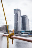 Rope tied around hook on handrail. Outdoor shot city by the water in background stock photo
