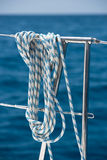 A rope tied around a lifeline on a yacht. Ocean background Stock Photos