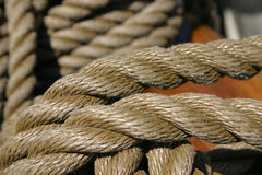 Rope tied around wooden cleat (extreme closeup). Extreme closeup of natural line tied around wooden cleat Royalty Free Stock Image
