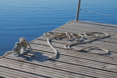 Rope tied up on a bitt on wooden dock. Blue water in the background Royalty Free Stock Photo