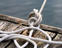 Rope Tied Up At Dock. Sturdy knotted rope tied up on boating dock Royalty Free Stock Image
