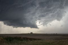 A rope tornado funnel dissipates underneath the updraft of a supercell thunderstorm. A rope tornado funnel dissipates underneath the updraft of a supercell stock image