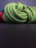 Rope used for climbing or by an arbotist or tree surgeon. Close up of climbing rope coil on blake background Royalty Free Stock Photography